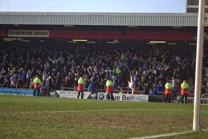 Oldham Athletic fans celebrate a 1-0 victory away to Crewe in league 1