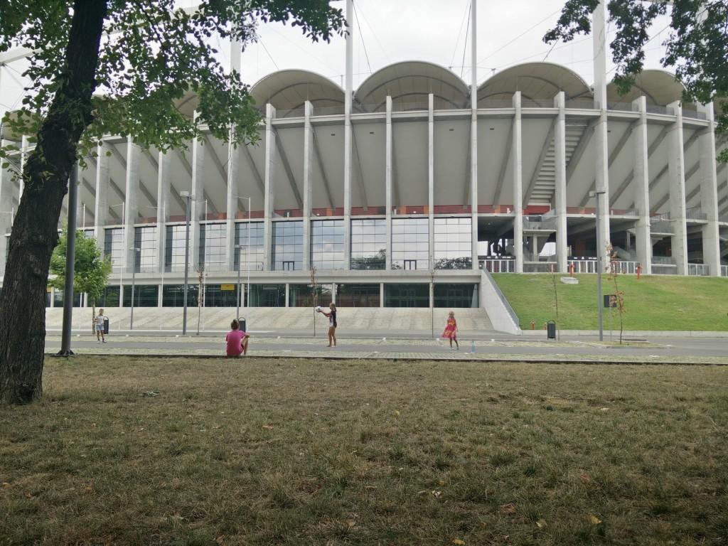 Kids playing outside stadium.
